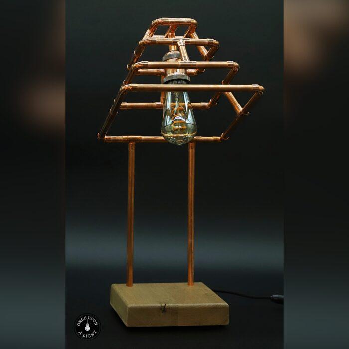 Lampe de table en forme de pyramide en cuivre sur son socle en chêne